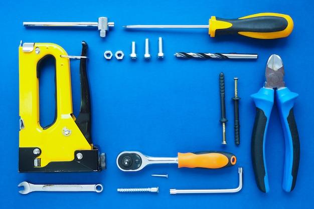 青色の背景にきちんとレイアウトされた、建設と修理のための手工具のセット。コピースペース。