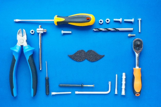 きちんとレイアウトされた修理用の手工具のセットと青色の背景に黒い光沢のある口ひげ。