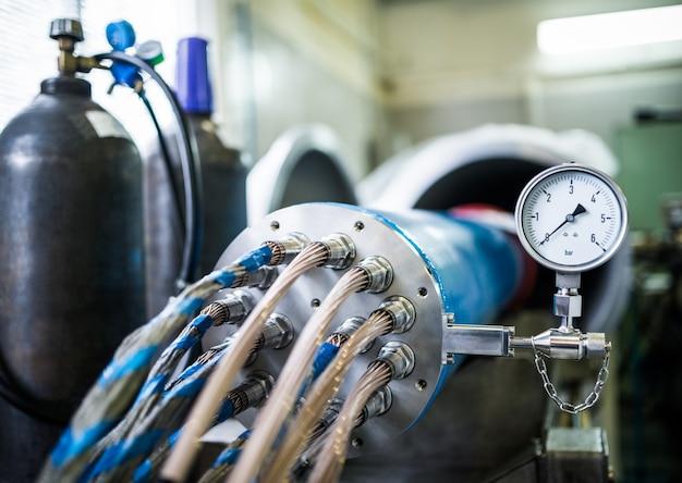 気圧計が接続された鉄製ドラムに装着された共通ノズル内の高電圧ケーブルのセット