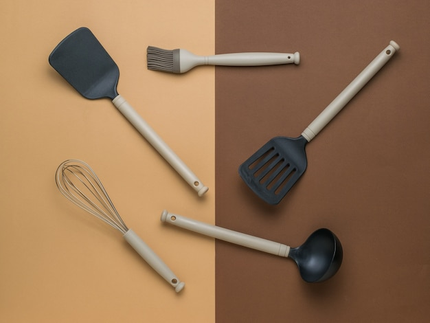Набор кухонных принадлежностей на двухцветном фоне. пластиковые кухонные инструменты. плоская планировка.