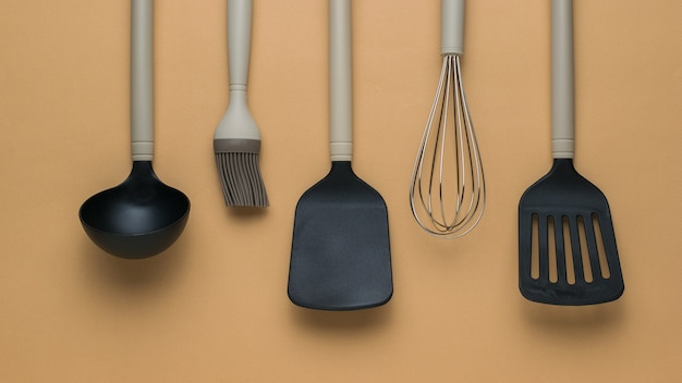 Набор кухонных принадлежностей с бежевыми ручками на светлом фоне. пластиковые кухонные инструменты. плоская планировка.