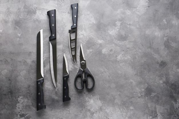 Набор ножей. различная кухонная утварь на сером столе