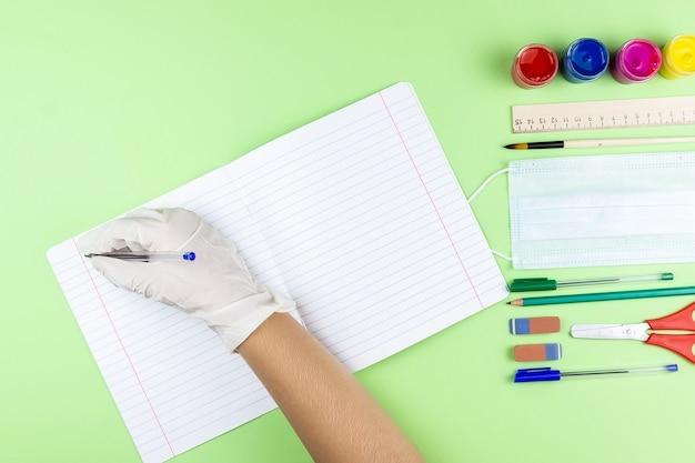 Набор концлярских школьнвх предметов с голубой медицинской маской на пастельно-зеленом фоне с местом для текста.