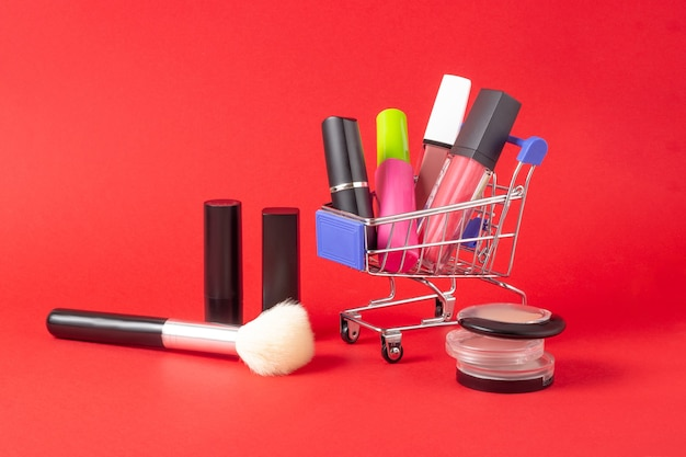 Набор косметики для губ и блесков для губ, пудра, тени для век и тележка для покупок на ярко-красном фоне. концепция покупки косметики, интернет-шоппинга, праздника