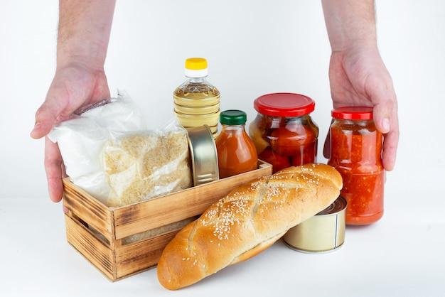 Набор продуктов длительного хранения и мужских рук на белой стене. пожертвования или концепция доставки еды