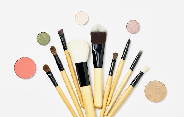 Набор кистей для макияжа с круглыми тенями, разбросанными на белом фоне. различные косметические кисти с разбросанными разными шариками теней для ухода за кожей. образец косметического продукта.