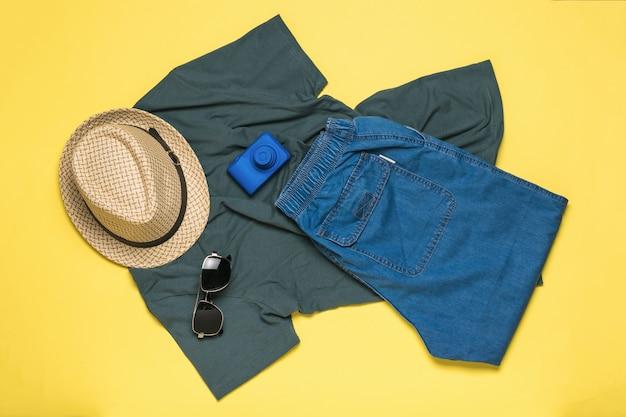 黄色の背景に紳士服と旅行アクセサリーのセット。フラットレイ。