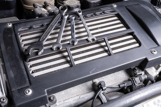 Набор металлических гаечных ключей разных размеров лежит под капотом автомобиля на масляном радиаторе.