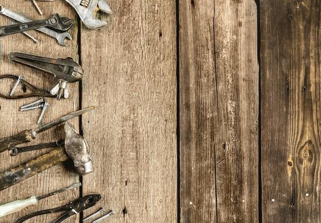 Набор металлических инструментов в мастерской на старом деревенском деревянном фоне