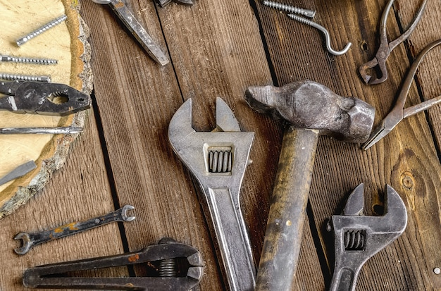 Набор металлических инструментов в мастерской на деревенском деревянном фоне