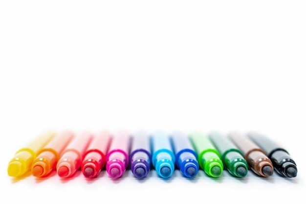 Набор разноцветных фломастеров в ряд, радуга на светлом белом фоне крупным планом. маркеры для рисования, карандаши, тушь, инструменты художника, творчество, досуг, хобби. красочные школьные принадлежности