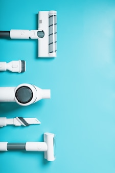 파란색 배경, 여유 공간에 연속으로 노즐과 흰색 무선 진공 청소기 세트. 평면도