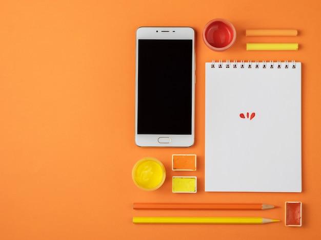 オレンジ色の背景に絵画用品のセット。上から見る