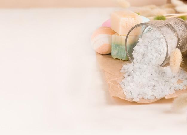 入浴用商品一式。白い背景の上の塩、石鹸、バスボム。スペースをコピーします。バナー