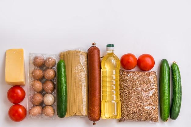 Набор продуктов на белом фоне. продовольственные товары, овощи, масло, яйца и колбаса. пищевая упаковка
