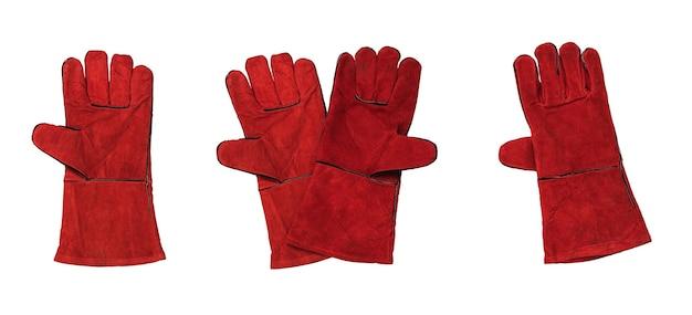 白い表面で絶縁された溶接機用の赤い手袋のセット。溶接作業用の保護アクセサリ。