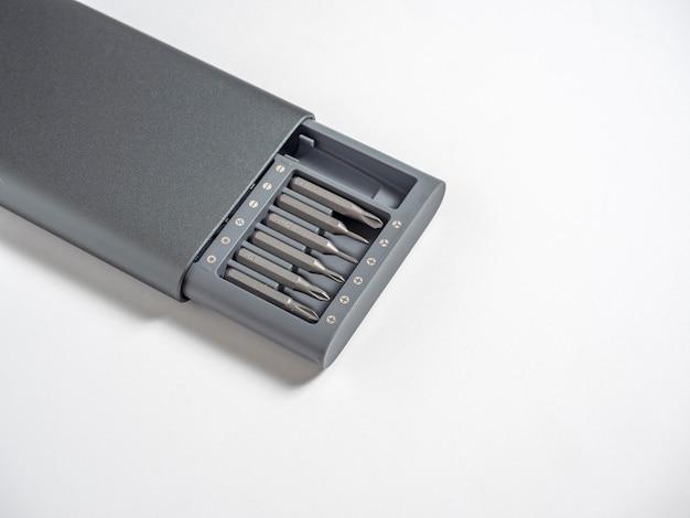 白い壁に隔離されたケースのビットとドライバーのセット。コピースペース、仕事のためのツール