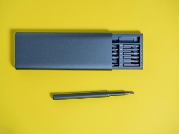 노란색 배경에 케이스에 비트가 있는 드라이버 세트. 작업을 위한 도구입니다. 드라이버는 세트 옆에 있습니다
