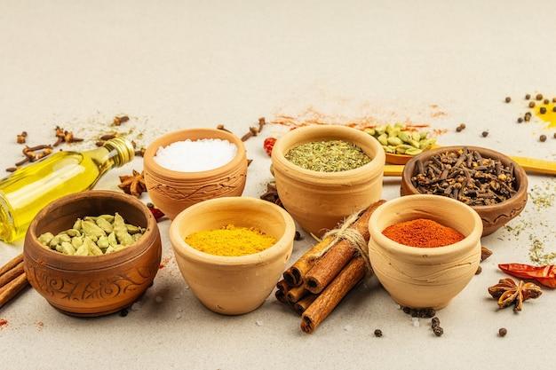 カレーを調理するためのスパイスのセット。芳香性調味料:ターメリック、パプリカ、カルダモン、シナモン、スターアニス、チリ、黒コショウ、ドライハーブ、塩。明るい石のコンクリートの背景、コピースペース