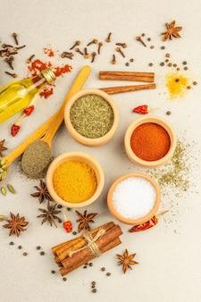 カレーを調理するためのスパイスのセット。芳香性調味料:ターメリック、パプリカ、カルダモン、シナモン、スターアニス、チリ、黒コショウ、ドライハーブ、塩。明るい石のコンクリートの背景、上面図