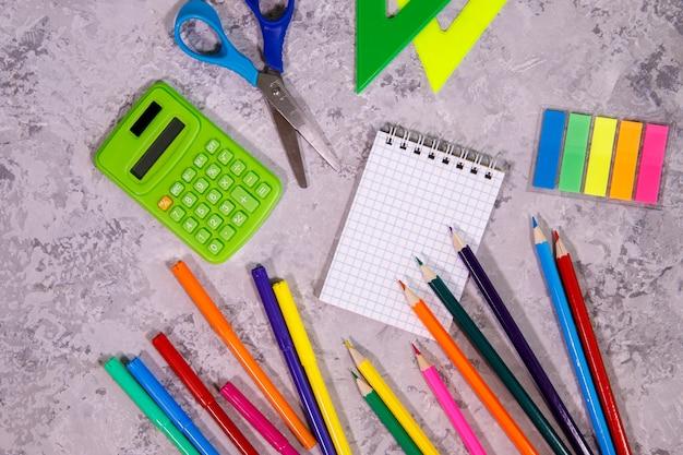 文房具のセット。メモ帳、電卓、色鉛筆、定規、フェルトペン、はさみ、カラフルなステッカー