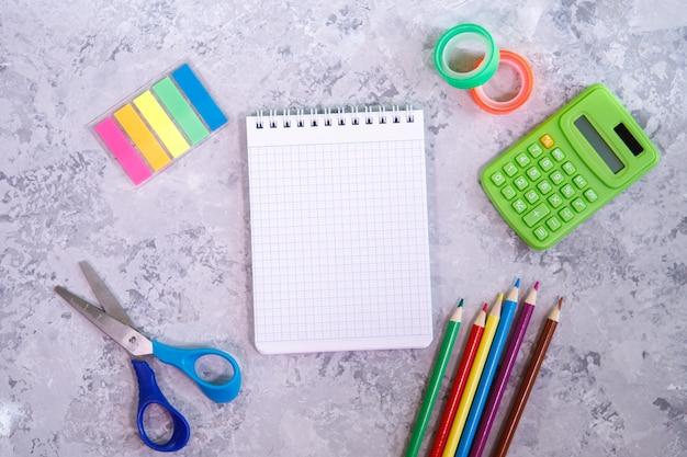 文房具のセット。メモ帳、色鉛筆、電卓、はさみ、カラフルなステッカー、スコッチテープ