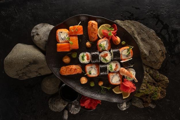 아름다운 검정 잉크 판에 초밥 세트. 사시미, 롤, 마키, 생강, 와사비, 땅콩 소스의 일식 요리