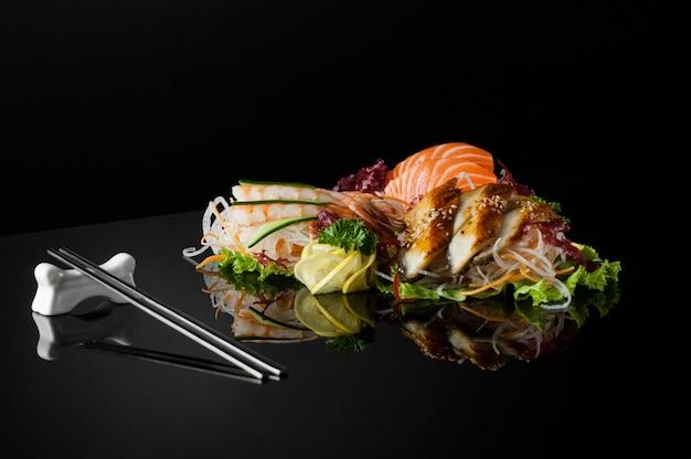 Набор суши с креветками и палочками для еды на черном фоне с отражением