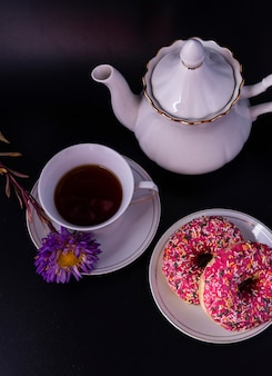 검은 배경에 장식과 꽃이 있는 다도 도넛 세트.
