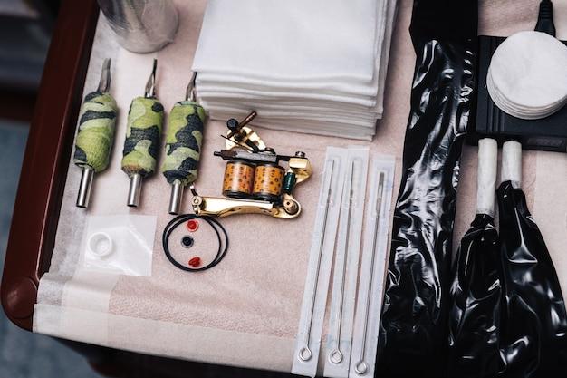 문신 예술가를 위한 도구 세트입니다. 바늘, 냅킨, 문신 기계, 교체 가능한 손잡이의 레이아웃.
