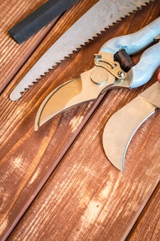 빈티지 나무 판자에 정원사를 위한 도구 세트는 봄에 정원을 가지치기 전에 준비됩니다