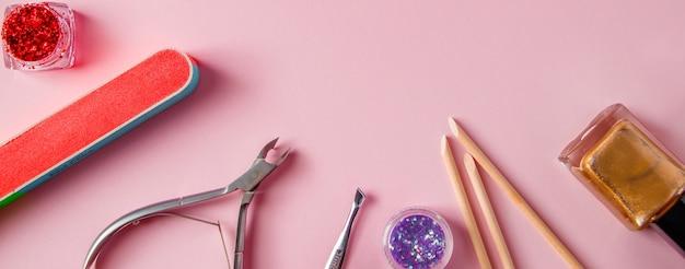 Набор инструментов для маникюра и ухода за ногтями на розовом фоне рабочее место в салоне красоты
