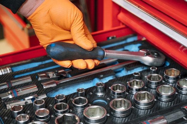 車のサービスで修理するためのツールのセット-整備士の手、クローズアップ。