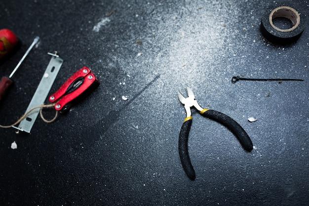 램프 자체 설치를위한 도구 세트는 하얀 먼지가 뿌려진 검은 테이블 위에 있습니다. 한 시간 동안 남편. 가사일.