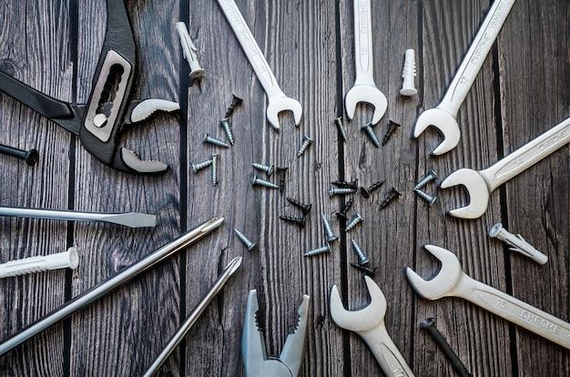 木製の背景上のツールのセット:ドライバー、ペンチ、モンキーレンチ、オープンエンドレンチ、ネジ、ダボ。