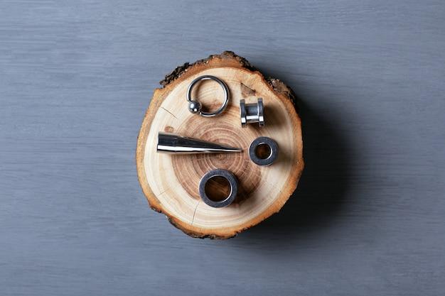 Набор необычных сережек и растяжек для пирсинга на куске дерева.