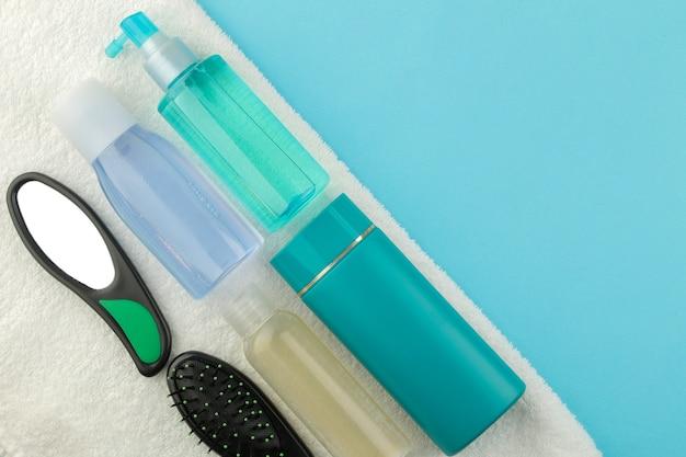 明るい青色の背景の白いタオルにさまざまなヘアコームと鏡と髪の化粧品のセット。上からの眺め。テキスト用のスペースあり