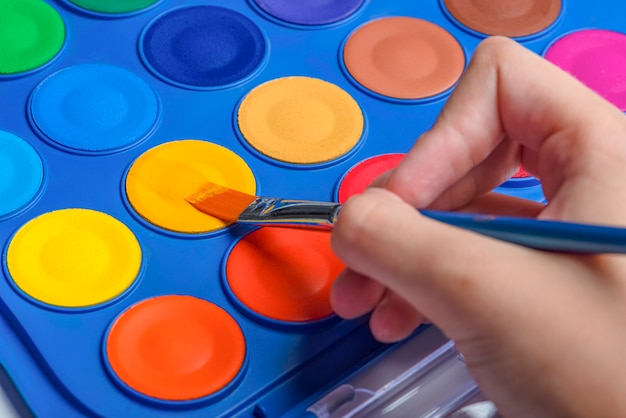 클로즈업을 그리기 위한 수채화 물감 세트와 브러시. 붓으로 아이의 손입니다. 선택적 초점입니다.
