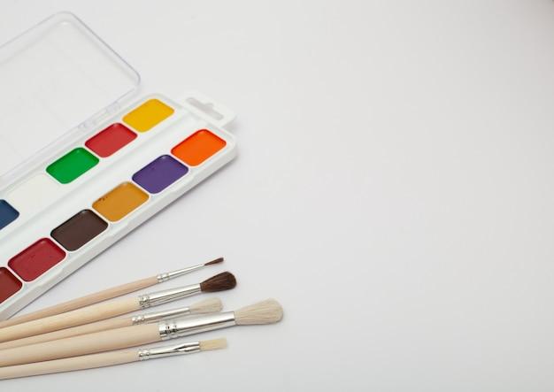 テキスト用のコピースペースを持つ白い背景の水彩絵の具とペイントブラシのセット。閉じる