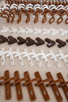 Набор металлических ручек белого и коричневого цвета и фурнитуры для пластиковых окон и дверей.