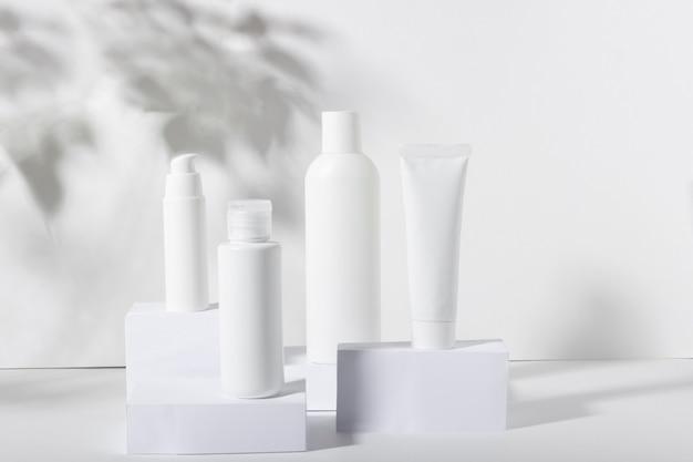 Набор белых косметических банок на квадратных подставках с тенями. зубная паста, крем для лица и тела, шампунь для волос. профессиональная косметика по уходу за кожей. органическая косметика.