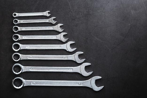 Набор гаечных ключей в ряд на черном фоне в ряд.