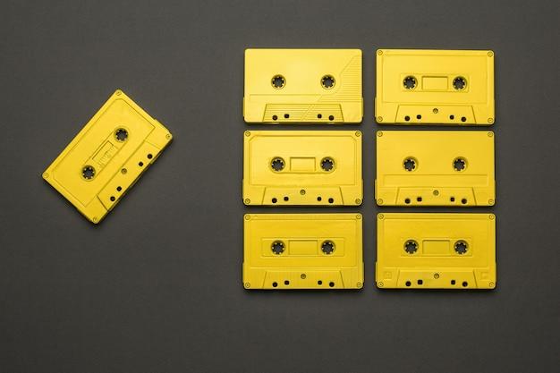 어두운 회색 배경에 테이프 레코더용 노란색 카세트 세트. 음악을 듣기 위한 세련된 복고풍 장비. 플랫 레이.