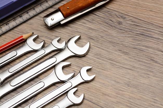 Комплект с инструментом на деревянном столе. молоток, отвертка, гаечные ключи, плоскогубцы, кусачки. вид сверху.