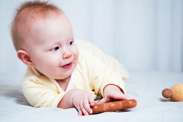 生後7か月の女の子は、明るい部屋でお腹に横になって、幸せで、笑顔で木のおもちゃで遊んでいます。