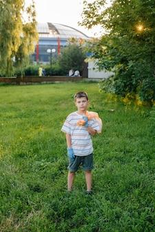 해질녘에 7세 소년이 공원에서 쓰레기 수거에 종사하고 있습니다. 환경 관리, 재활용.