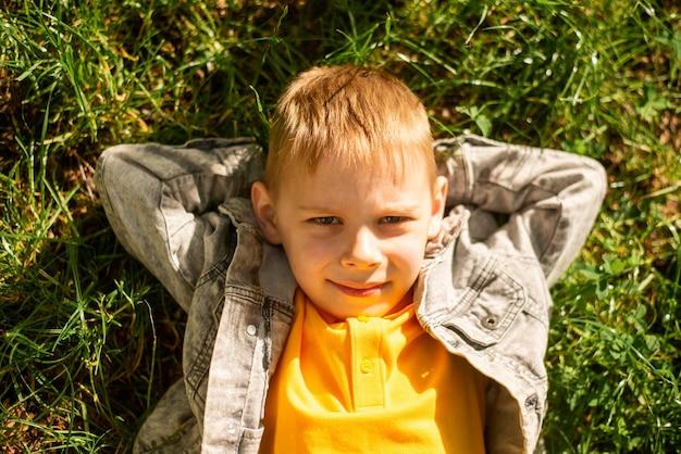 여름에 잔디밭에 누워있는 7세 소년
