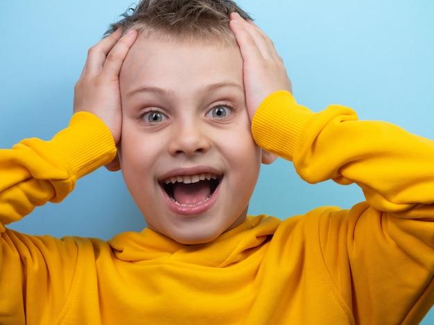7세 소년이 파란색 배경의 카메라 앞에서 손으로 머리를 잡고 놀라움을 보여주며 포즈를 취하고 있다