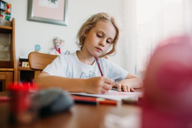 7歳の少女が自宅のテーブルに座ってノートに書き込み、学習タスクを完了したり、レッスンを繰り返したりします。