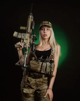 Сексуальная девушка в военном страйкбольном комбинезоне позирует с пистолетом в руках на темном фоне